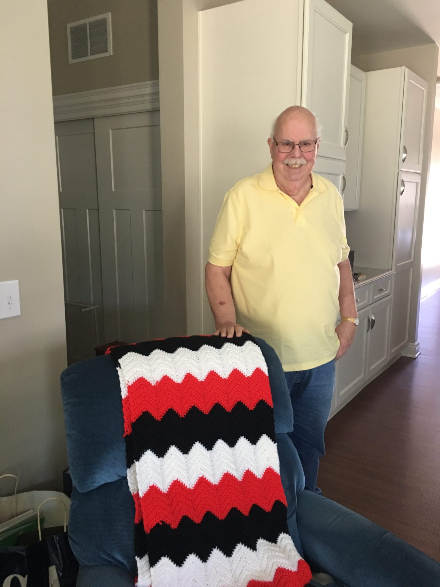 Man Smiling Next to Quilt